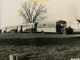 Line of school buses in front of a barn circa 1949
