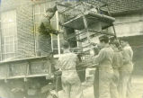 F.F.A. boys loading chicken brooder into the back of a truck outside Shawnee Mission High School...
