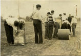 11 F.F.A. boys fertilizing and using a concrete lawn roller on a field